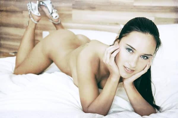 escort que esta posando encima de una cama y desnuda
